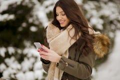 Uśmiechnięta młoda kobieta z telefonem komórkowym w zimie outdoors zdjęcia royalty free