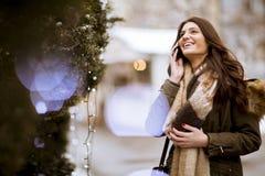 Uśmiechnięta młoda kobieta z telefonem komórkowym w zimie outdoors obraz royalty free