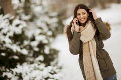 Uśmiechnięta młoda kobieta z telefonem komórkowym w zimie outdoors zdjęcia stock