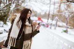 Uśmiechnięta młoda kobieta z telefonem komórkowym w zimie outdoors zdjęcie royalty free