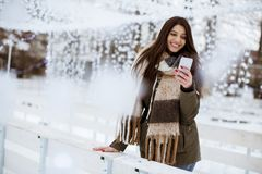 Uśmiechnięta młoda kobieta z telefonem komórkowym w zimie outdoors obrazy royalty free