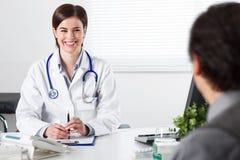 Uśmiechnięta Młoda kobiety lekarka słucha pacjent Obrazy Royalty Free