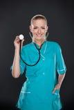 Uśmiechnięta młoda kobiety lekarka w zieleń mundurze. obraz stock