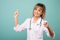 Uśmiechnięta młoda kobiety lekarka z stetoskopu punktami w górę kamery z ona w i palce zdjęcia stock