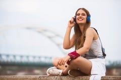 Uśmiechnięta młoda miastowa kobieta używa mądrze telefon outdoors podczas gdy czekać na jej przyjaciół zdjęcia stock