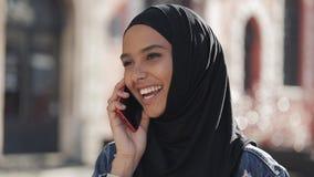 Uśmiechnięta młoda muzułmańska kobieta jest ubranym hijab chustkę na głowę opowiada z przyjaciółmi na smartphone w mieście, dama  zbiory wideo