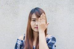 Uśmiechnięta młoda piękna azjatykcia kobieta zamyka ona oczy z rękami na betonowej ściany tle Obrazy Stock