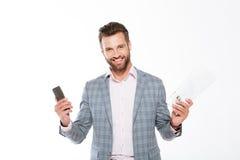 Uśmiechnięta młodego człowieka mienia urzędówka i telefon komórkowy Zdjęcie Royalty Free