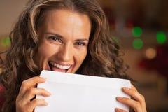 Uśmiechnięta młodej kobiety oblizania koperta Zdjęcia Royalty Free