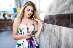 Uśmiechnięta młodej kobiety pozycja z telefonem blisko budynku na lata miasta ulicie Zdjęcie Royalty Free