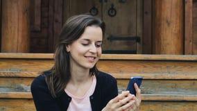 Uśmiechnięta młodej kobiety przesyłanie wiadomości na wiszącej ozdobie i uczucie zachwycający zdjęcie wideo