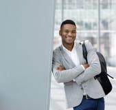 Uśmiechnięta młody człowiek pozycja przy lotniskiem z torbą Zdjęcia Stock