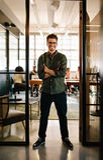 Uśmiechnięta młody człowiek pozycja w drzwi biuro Zdjęcia Stock