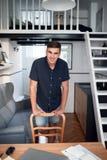 Uśmiechnięta młody człowiek zawartość w jego loft mieszkaniu Fotografia Royalty Free