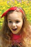 Uśmiechnięta mała ładna dziewczyna w żółci kwiaty Czerwone kępki dalej Obrazy Royalty Free
