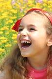 Uśmiechnięta mała ładna dziewczyna w żółci kwiaty Czerwone kępki dalej Obrazy Stock