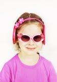Uśmiechnięta mała śliczna dziewczyna jest ubranym różowych okulary przeciwsłonecznych obrazy royalty free