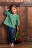 Uśmiechnięta mała afrykańska dziewczyna w wiejskiej koszula z wiązką jagody na tle brown drewniana ściana obraz royalty free