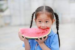 Uśmiechnięta mała Azjatycka dziecko dziewczyna w mundurku szkolnym cieszy się łasowanie arbuza outdoors fotografia stock