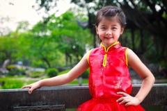 Uśmiechnięta mała azjatykcia dziewczyna w chińskiego stylu sukni Zdjęcia Royalty Free