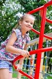 Uśmiechnięta mała dziewczynka bawić się na boiska wyposażeniu Zdjęcie Stock