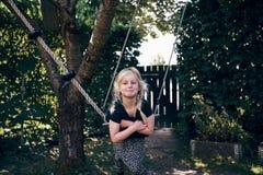 Uśmiechnięta mała dziewczynka bawić się na drzewnej huśtawce outdoors zdjęcia royalty free
