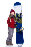 Uśmiechnięta mała dziewczynka jest ubranym trykotowego pulower, szalika, kapelusz i rękawiczki z błękitnym snowboard z kędzierzaw obrazy stock