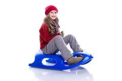 Uśmiechnięta mała dziewczynka jest ubranym z kędzierzawą fryzurą trykotowego puloweru, szalika i kapeluszu obsiadanie na saniu, o obraz stock