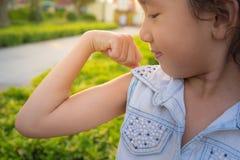 Uśmiechnięta mała dziewczynka pokazuje jej ręka bicepsów mięśni siłę Obraz Royalty Free