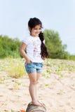 Uśmiechnięta mała dziewczynka pozuje chodzić wzdłuż brzeg Obrazy Royalty Free