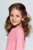 Uśmiechnięta mała dziewczynka przeciw szaremu tłu zdjęcie stock