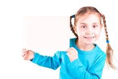 Uśmiechnięta mała dziewczynka trzyma biel kartę dla ciebie pobiera próbki tekst fotografia royalty free