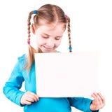 Uśmiechnięta mała dziewczynka trzyma biel kartę dla ciebie pobiera próbki tekst obraz royalty free