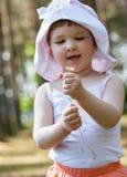 Uśmiechnięta mała dziewczynka trzyma stokrotki Fotografia Royalty Free