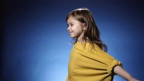 Uśmiechnięta mała dziewczynka w żółtym przędzalnictwie Błękitny tło, zwolnione tempo zbiory wideo
