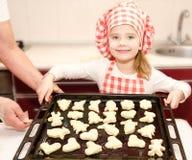 Uśmiechnięta mała dziewczynka w szefa kuchni kapeluszu z wypiekowym prześcieradłem ciastka fotografia royalty free