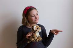 Uśmiechnięta mała dziewczynka wskazuje coś jej pluszowa zabawka zdjęcia stock
