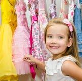 Uśmiechnięta mała dziewczynka wybiera suknię od garderoby Obrazy Royalty Free