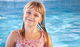 Uśmiechnięta mała dziewczynka z jaskrawą błękitną basen wodą Fotografia Royalty Free