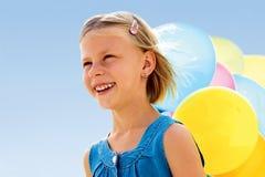 Uśmiechnięta mała dziewczynka z kolorowymi balonami Fotografia Stock