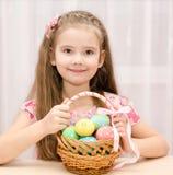 Uśmiechnięta mała dziewczynka z koszykowy pełnym kolorowi Easter jajka Zdjęcie Stock