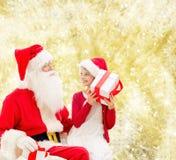 Uśmiechnięta mała dziewczynka z Santa Claus i prezenty Obrazy Royalty Free