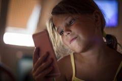 Uśmiechnięta mała dziewczynka z telefonem komórkowym zdjęcie stock