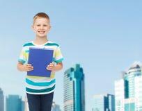 Uśmiechnięta mała studencka chłopiec z błękitną książką Obrazy Royalty Free