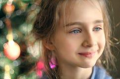 Uśmiechnięta małe dziecko dziewczyna, dekorująca choinka jako blurr Fotografia Royalty Free