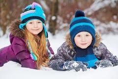 Uśmiechnięta małej dziewczynki i chłopiec kłamstwa strona popiera kogoś na snowdrift - obok - fotografia stock