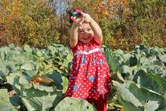 Uśmiechnięta małej dziewczynki pozycja wśród kapusty z ona up ręki zdjęcie stock