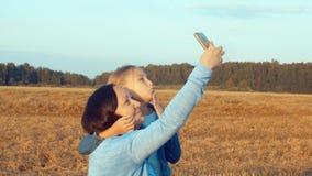 Uśmiechnięta matka i grimacing córka bierze selfie na telefonie w pszenicznym polu zbiory wideo