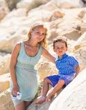 Uśmiechnięta matka i jej mały syn Kolorów żółtych kamienie i skały Pojęcie matka dzień Rodziny outdoors portret Fotografia Stock