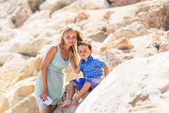Uśmiechnięta matka i jej mały syn Kolorów żółtych kamienie i skały Pojęcie matka dzień Rodziny outdoors portret Zdjęcie Stock